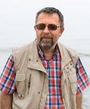 Ruhiger sorgloser älterer Mann auf dem Seehintergrund Stockbild