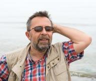 Ruhiger sorgloser älterer Mann auf dem Seehintergrund Lizenzfreie Stockfotografie