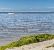 Ruhiger Tag an der Bucht mit einem grauen Boot auf dem Wasser des ruhigen Sees Stockfotografie