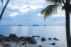 Ruhiger tropischer Sonnenuntergang auf einem Hintergrund von Palmen und von felsigem Ufer Lizenzfreies Stockbild