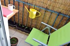 Ruhiger und gemütlicher Platz für entspannen sich im kleinen Balkon, kleine Anlagen im Töpfe arround Grünstuhl Lizenzfreies Stockbild