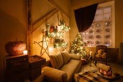 Ruhiges Bild des modernen Hauptinnenwohnzimmers verzierte Weihnachtsbaum und Geschenke, Sofa, die Tabelle, die mit Decke bedeckt  Stockbild