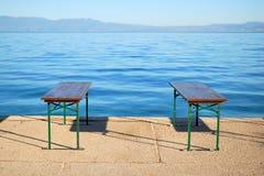 Ruhiges blaues Meer und zwei Bänke Stockfoto