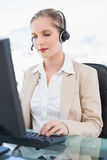 Ruhiges blondes Call-Center-Mittel, das an Computer arbeitet Lizenzfreies Stockbild