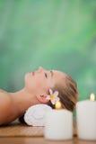 Ruhiges blondes Lügen auf Bambusmatte mit Kerzen Stockfotografie