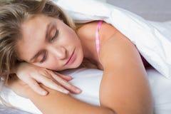 Ruhiges blondes Lügen auf ihrem Bett schlafend Stockbild