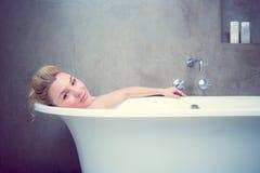 Ruhiges blondes Lügen im Bad, das an der Kamera lächelt Lizenzfreie Stockbilder