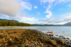 Ruhiges felsiges Seeufer mit fantastischen Ansichten der Berge Stockfotos