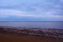 Ruhiges flaches Meer, felsiger Strand und bewölkter Himmel, Nordmeer, Holkham-Strand, Vereinigtes Königreich Lizenzfreie Stockfotografie