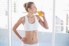 Ruhiges junges blondes Modell, das Orangensaft genießt Lizenzfreie Stockbilder