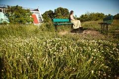 Ruhiges junges Mädchen, das auf einer Bank auf einem Gebiet mit Gras und Wildflowers sitzt Lizenzfreie Stockbilder