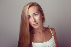 Ruhiges nachdenkliches kaukasisches blondes junges schönes Mädchenfrauenmodell mit dem langen Haar und den blauen Augen im weißen Stockfotografie