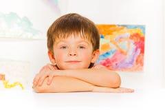 Ruhiges Porträt des kleinen Jungen auf dem Tisch gelegt Lizenzfreie Stockfotografie