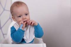 Ruhiges Schönheitskleinkind im Babystuhl in der Küche Stockfoto