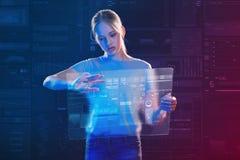 Ruhiges Schulmädchen, das ein transparentes Gerät hält lizenzfreies stockbild