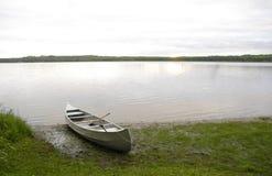 Ruhiges Ufer und Kanu an der Dämmerung lizenzfreie stockfotos