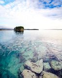 Ruhiges Wasser mit Steinen und Sonnenuntergang bewölkt sich über Meer mit Insel Lizenzfreies Stockfoto