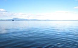 Ruhiges Wasser und ein Berg Stockbild