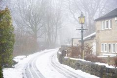 Ruhiges Winterstraßenbild mit Schnee und Nebel Stockfotografie