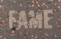 Ruhm geschrieben in weiße Großbuchstaben auf eine Straßenpflasterung Lizenzfreies Stockbild