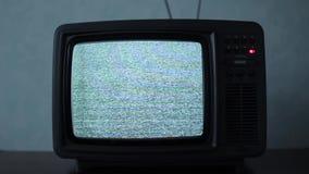 Ruido estático en un aparato de TV del vintage en un cuarto oscuro almacen de video