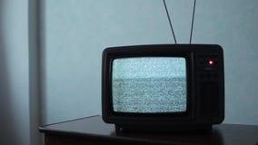 Ruido estático en un aparato de TV del vintage en un cuarto oscuro almacen de metraje de vídeo