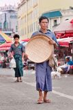 Traditional dressed manwalks on a market place in Ruili, Yunnan Province, China stock photos