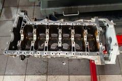 Ruilmotor op een kraan opgezet voor installatie op een auto na een analyse en een reparatie in een workshop van de autoreparatie  stock fotografie
