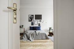 Ruim en natuurlijk slaapkamerbinnenland met hardhoutvloer, kunstgalerie en minimalistisch decor royalty-vrije stock foto