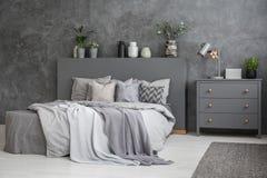 Ruim grijs en wit slaapkamerbinnenland met groot bed met bed stock foto