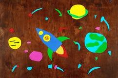 Ruimteraket en planeten, zonnestelsel, Ruimtevaart en sterren op houten die achtergrond-toepassing door kind wordt gemaakt Royalty-vrije Stock Foto's