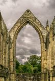 A ruin of an abbey from a bygone age. A derelict ruin of a church, abbey, monastery or convent. large open archways. arched windows. rain clouds gathering in royalty free stock photo