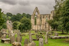 A ruin of an abbey from a bygone age. A derelict ruin of a church, abbey, monastery or convent. large open archways. arched windows. rain clouds gathering in stock photos