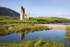 Ruin of ancient Scottish castle. With pools of water and green grass in front and blue sky in the background Stock Photography