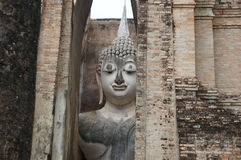Ruin of Buddha face behind stone wall, Thailand Stock Photo