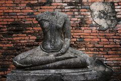 Ruin Buddha statue without head, Ayutthaya. Ruin Buddha statue without head near old grunge brick wall with copy space for text in Ayutthaya, Thailand stock images