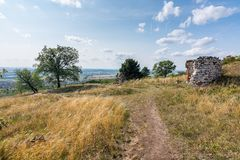 Ruin of the chapel and stone wall on meadow, with trees and grass. Summer weather with blue sky.  Stock Photo