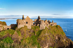 Ruin of Dunluce castle in Northern Ireland. Ruins of Dunluce castle in County Antrim, Northern Ireland, UK, with the far view of  Portrush resort on the left Stock Photo