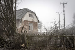 The ruin of the house in the fog. In the small village Stock Image