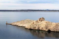 Ruin and lighthouse on an island Stock Photos