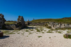 Ruin of Llanddwyn chapel, Anglesey, cross and lighthouse in dist. Grounds of ruined chapel or church on Llanddwyn Island,  a peninsula on Anglesey. Newborough Stock Photography