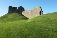 Ruin of medieval fortress. Sitting on grassy hill Stock Image