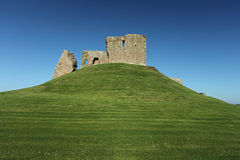 Ruin of medieval fortress. Sitting on grassy hill Stock Photography
