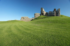 Ruin of medieval fortress sitting on grassy hill Royalty Free Stock Photography