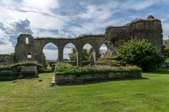 Ruin of a medieval monastery in summertime. Ruin of a medieval monastery or cloister located in Alvastra, Sweden. On a beautiful sunny summer day with green Stock Image