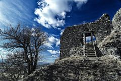 Ruin of the old castle with wooden stairs under the deep blue sky Stock Photography