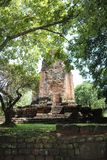 The ruin pagoda of Prang Srithep and foreground green tree in archaeological site of Srithep ancient town in Petchaboon, Thailand. The influence of ancient Stock Photo