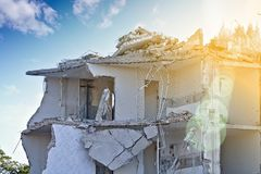 Ruin of a partly demolished residential building upper floor, sunlit with lens flare. Ruin of a partly demolished residential building upper floor in front of a Royalty Free Stock Photo