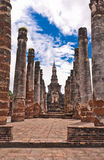 Ruin pillars and pagoda in back in sukhothai. Historic park Thailand Stock Image
