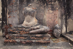 Ruin sitting Buddha statue with the head beside Stock Photos